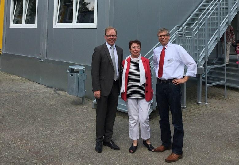 Sozialamtsleiter Jürgen Hages, Angelika Quiring-Perl, Stadtverordnete für Reuschenberg, und Marc Dietrich, Leiter des DRK Neuss vor den Wohncontainern am Südpark.