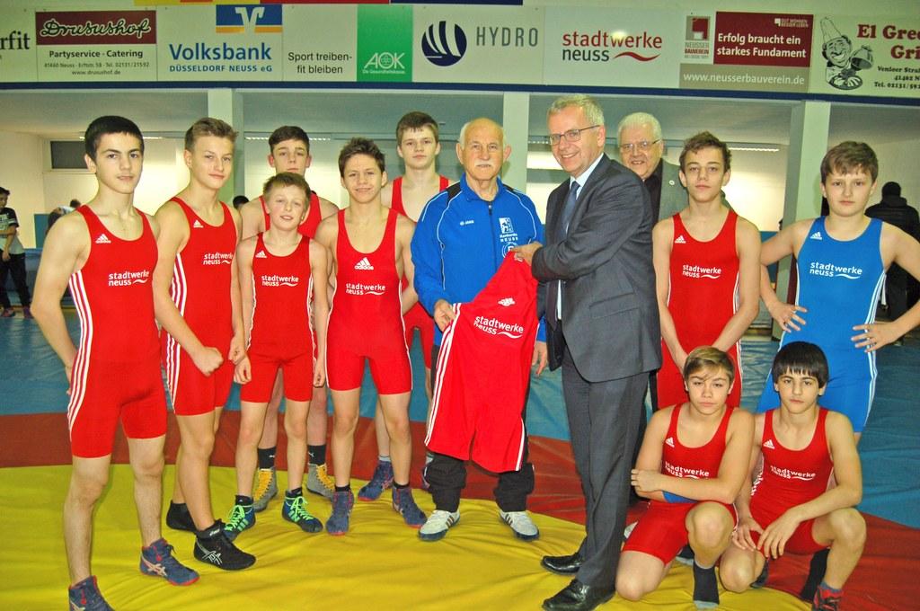 Stadtwerke-Geschäftsführer Stephan Lommetz übergibt die neuen Trikots im Beisein des KSK Konkordia-Ehrenvorsitzenden Hermann J. Kahlenberg an die B-Jugend-Ringer von Trainer Oleg Dubov.