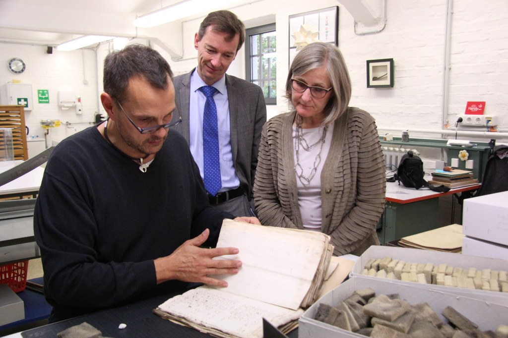 Kulturdezernentin Dr. Christiane Zangs lässt sich von Archivleiter Dr. Jens Metzdorf (m.) und Marcus Janssens, Leiter der Restaurierungswerkstatt des Stadtarchivs, die beschädigten Dokumente zeigen, die nun mit Fördermitteln des Bundes restauriert werden.