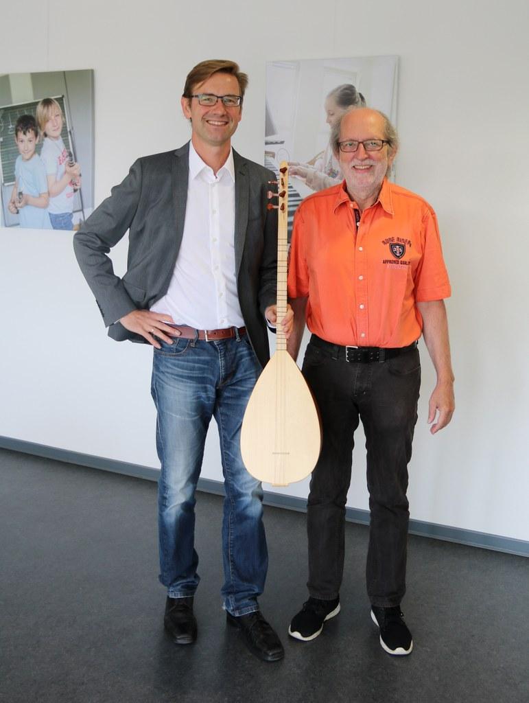 Musikschulleiter Holger Müller und sein Stellvertreter Jochen Büttner mit der Langhalslaute bağlama, für die Unterricht ab Oktober neu im Programm ist.