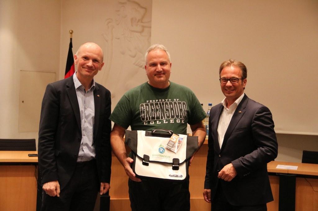Bürgermeister Reiner Breuer (r.) und Dr. Matthias Welpmann, Umwelt-, Klima- und Sportdezernent, übergeben die Fahrradtasche an Volker Nickel.