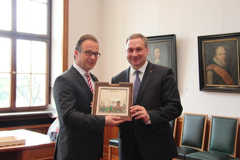 Der Stadtpräsident von Pskow, Ivan Zezerski (r.), überreicht Bürgermeister Reiner Breuer eine Uhr, auf der Motive aus Neuss und Pskow verbunden sind.
