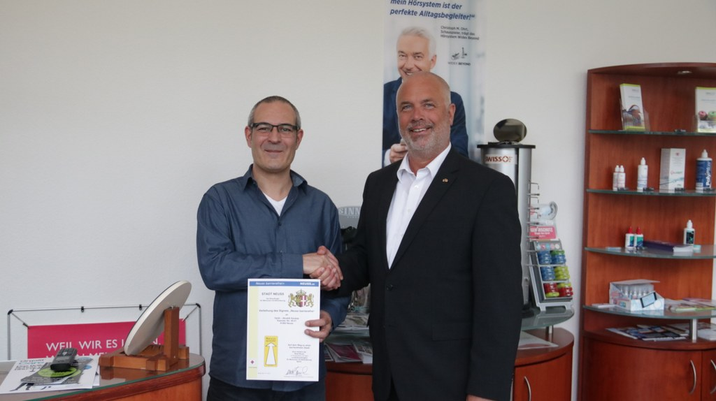 Sozialdezernent Ralf Hörsken (r.) überreicht Askan Karatas die Verleihungsurkunde.