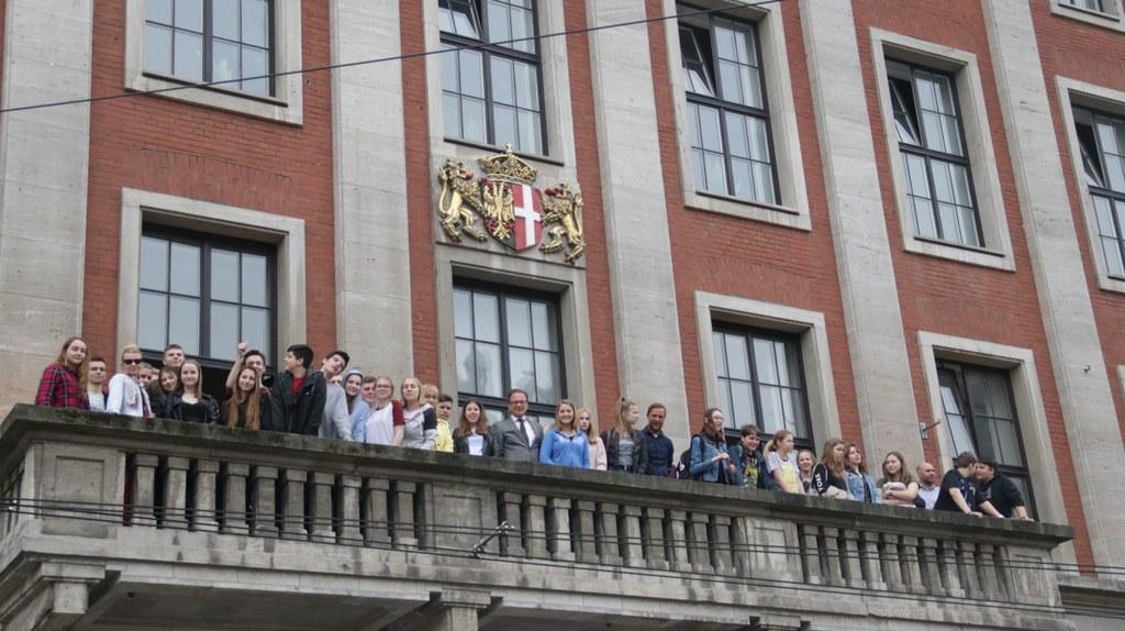 Bürgermeister Reiner Breuer zeigt den Schülerinnen und Schülern aus Warschau Neuss vom Rathausbalkon.