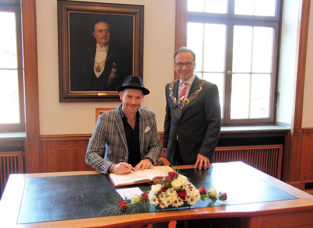 Danny aus den Birken mit Bürgermeister Reiner Breuer bei seinem Eintrag in das Goldene Buch der Stadt Neuss.