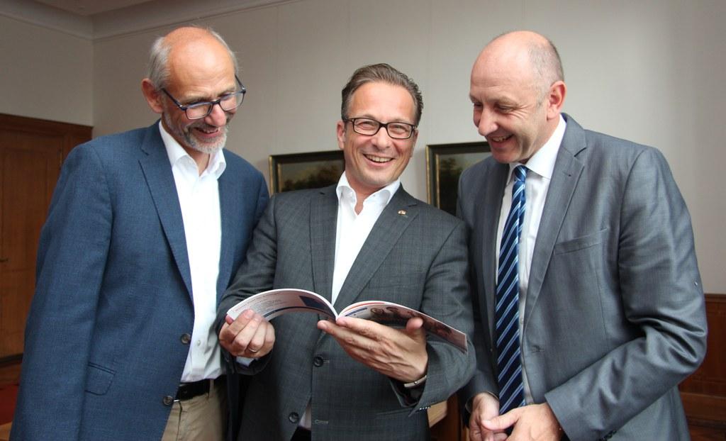 (v.r.) Jürgen Sturm, Leiter Neuss Marketing, Bürgermeister Reiner Breuer, und Uwe Neumann, Leiter Bürger- und Ordnungsamt, freuen sich über die gelungene Broschüre für Neubürgerinnen und Neubürger.
