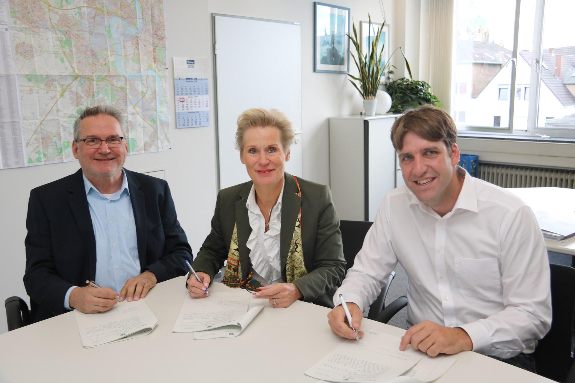 (v.l.) Helge Wallmeier, stellvertretender Jugendamtsleiter; Astrid Ficinus, Aufsichtsbeamtin für Grundschulen im Rhein-Kreis Neuss; und Achim König, Programmleiter Education Y, unterzeichnen den Vertrag.