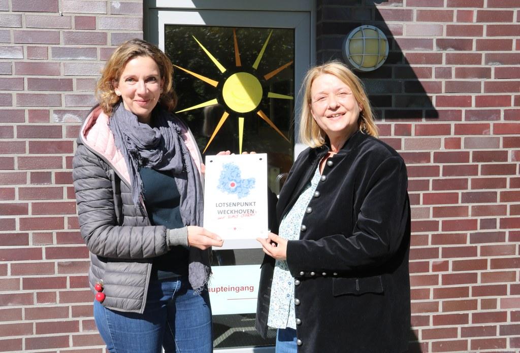 Gudrun Jüttner vom Sozialamt (l.) überreicht Birigt Adams, Leiterin des neuen Lotsenpunktes, das offizielle Schild.
