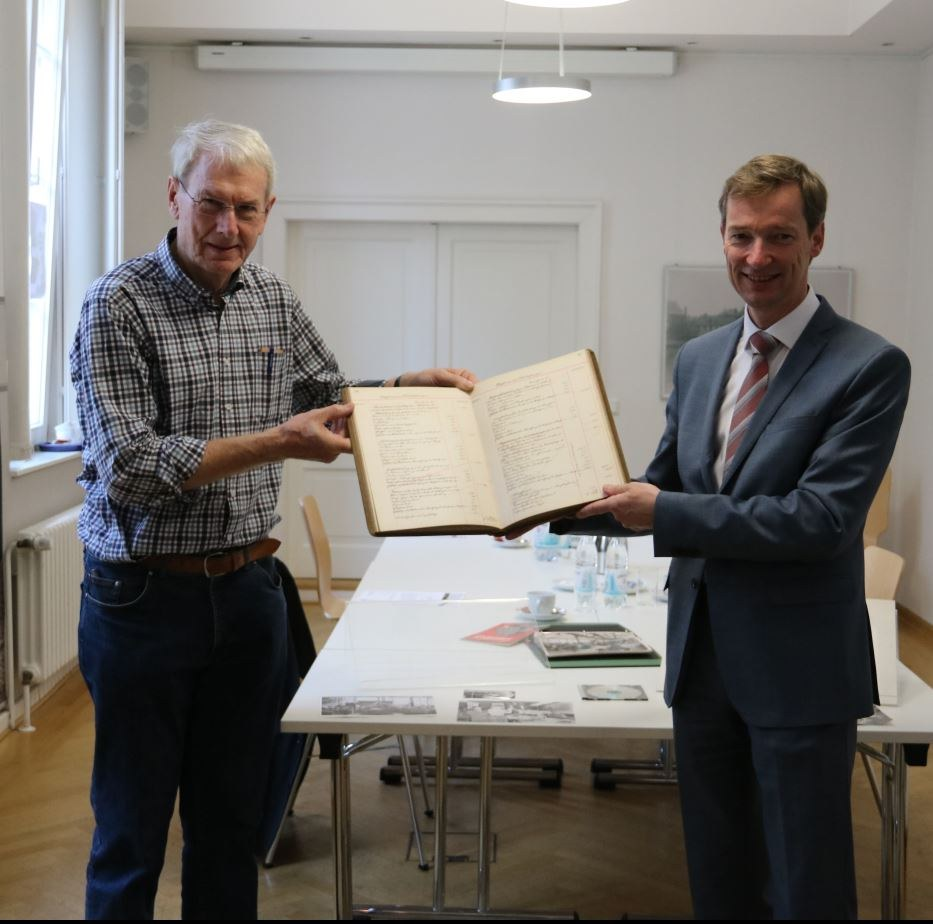 Dr. Albert Wunsch übergibt Archivleiter Dr. Jens Metzdorf ein Anlagenbuch von Bauer & Schaurte.