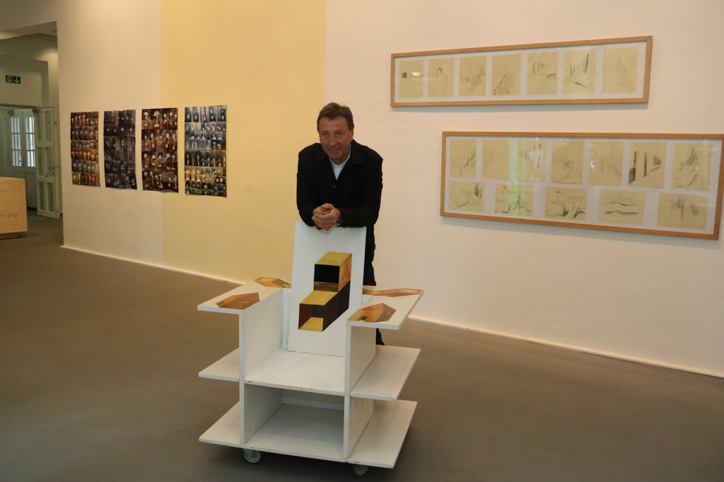 """Kurator Klaus Richter mit dem """"Büchersitz"""", einem Bibliotheksstuhl inmitten der Ausstellung."""