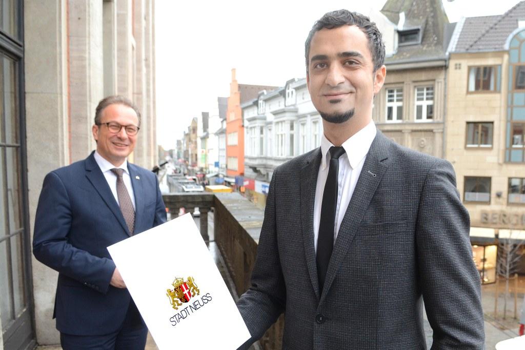 Bürgermeister Reiner Breuer überreicht Deniz Elbir die Ernennungsurkunde zum Beauftragten für Diversität, Integration und Antirassismus