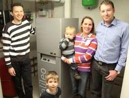 """Innovative Zukunftstechnik, aber nicht größer als eine Kühl-Gefrier-Kombination: Gregor und Tamara Mönks (rechts im Bild) und Familien-nachwuchs Maximilian und Jonathan freuen sich über ihr neues kompak-tes """"Kellerkraftwerk"""", das Sanitär- und Heizungsexperte Alexander Sta-mos (links) und sein Team erfolgreich installiert haben."""