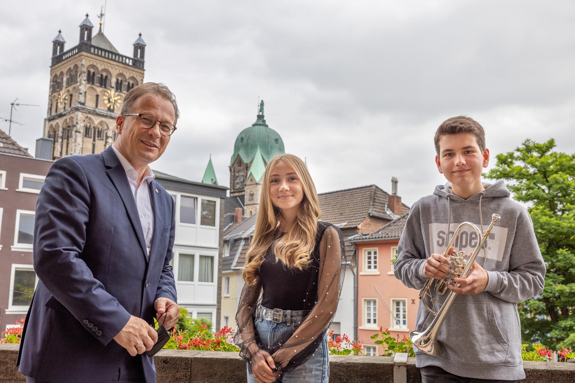 Bürgermeister Breuer und die beiden Preisträger von Jugend Musiziert auf dem Rathausbalkon