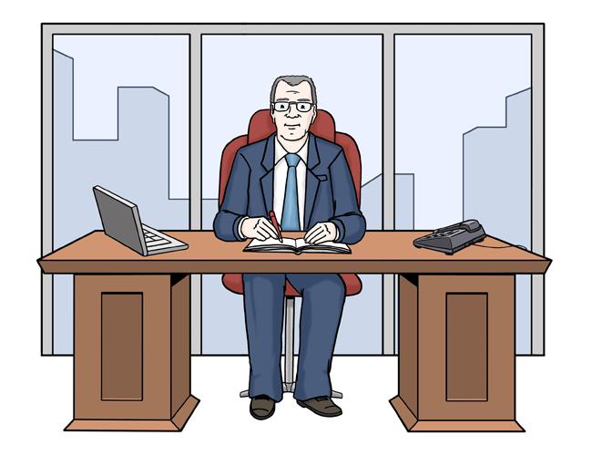 Der Chef sitzt im Büro am Schreibtisch.