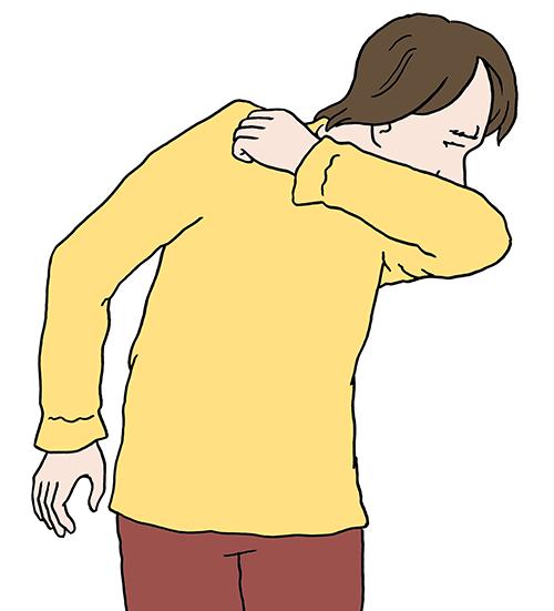 Ein Mann niest in die Arm-Beuge.